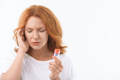 Frustrated lady curing her head against pain Stock Image
