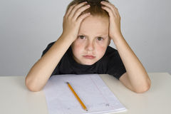 Frustrated little boy doing homework Stock Images
