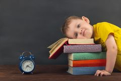 The frustrated little boy put his head on a stack of textbooks. Back to school. Doesn`t want to do his homework. stock photo