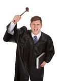 Frustrated male judge with gavel and book Stock Image