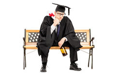 Frustrated male student seated on bench holding bottle of beer Stock Photos
