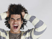 Frustrated Man With Afro Hairdo Pulling Hair Royalty Free Stock Photos