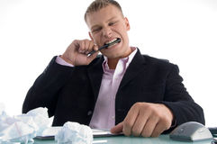 Frustrated man biting on pen with teeth Stock Photos