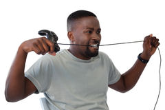 Frustrated man biting a wire of joystick Stock Photography