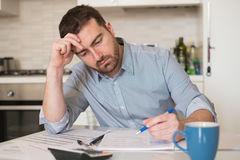 Frustrated man calculating bills expenses. Frustrated man calculating bills and tax  expenses Royalty Free Stock Photo