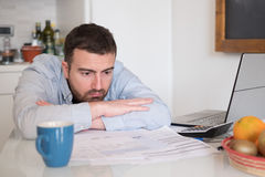 Frustrated man calculating bills and tax  expenses. Frustrated man calculating bills and tax expense Stock Photo