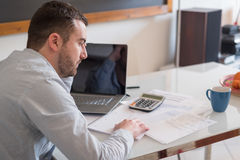 Frustrated man calculating bills and tax outcomes. Frustrated man calculating bills and tax  expense Stock Images