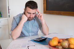Frustrated man calculating bills and taxes  expenses. Frustrated man calculating bills and tax  expenses Stock Photography