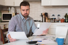 Frustrated man calculating bills and taxes  expenses Stock Image