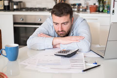 Frustrated man calculating bills and taxes. Frustrated man calculating bills and tax  expenses Royalty Free Stock Photo