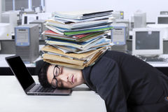 Frustrated man with document sleeping in office Royalty Free Stock Photos