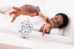 Frustrated man in front of alarm clock Royalty Free Stock Images