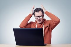 Frustrated man in glasses behind a laptop. Royalty Free Stock Photos