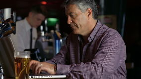 Frustrated man having a pint at  the bar using laptop stock video