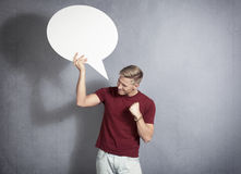 Frustrated man holding white blank speech bubble. Royalty Free Stock Photography