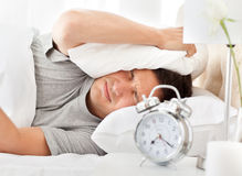 Frustrated man listening to his alarm clock Stock Photography