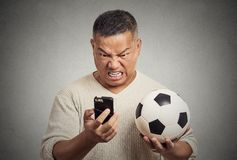 Frustrated man looking on cell smart phone watching game holding football Stock Image