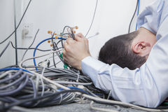 Frustrated man lying down trying to figure out and sort  computer cables Royalty Free Stock Photography