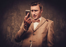 Frustrated man with mobile phone wearing jacket and bow tie Stock Image