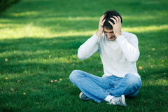 Frustrated man outdoors. Young man sitting on the grass holding head in frustration Royalty Free Stock Photography