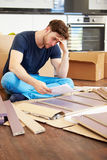 Frustrated Man Putting Together Self Assembly Furniture. Close Up Of Frustrated Man Putting Together Self Assembly Furniture Whilst Sitting On Floor stock photos