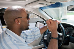 Frustrated Man With Road Rage. An irritated man driving a car is expressing his road rage with his fist clenched in the air Stock Image