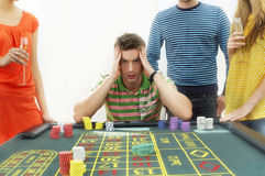 Frustrated Man At Roulette Table With Friends. Young frustrated men at roulette table with midsection of friends royalty free stock images