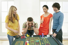 Frustrated Man At Roulette Table With Friends Stock Photo