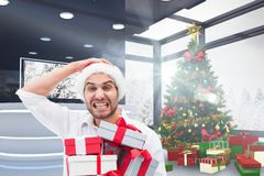 Frustrated man in santa hat holding gift boxes. During christmas time stock images
