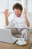 Frustrated man shouting in front of laptop at home Royalty Free Stock Photo