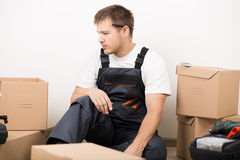 Frustrated man sitting between brown carton boxes Royalty Free Stock Photos