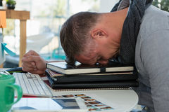 Frustrated man sleeping on files in office Stock Photo