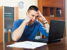 Frustrated man studying financial information on laptop Stock Image