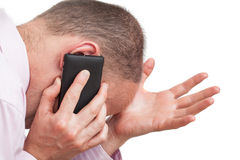 Frustrated man talking on the phone. On isolated white background Royalty Free Stock Photo
