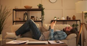 Frustrated man text messaging on mobile phone at home