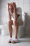 Frustrated man on toilet seat Royalty Free Stock Photo
