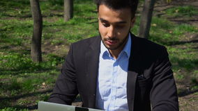 Frustrated man waiting e-mail from bank on laptop. Man sits by table and near laptop and waiting. Guy dressed in black jacket and blue shirt. Man has beard stock footage