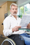 Frustrated Man In Wheelchair Reading Letter Stock Photography