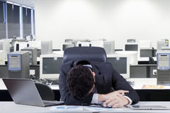 Frustrated manager sleeping in office room. Stressful male entrepreneur wearing formal suit and sleeping on the table with laptop and documents, shot in the Stock Photo