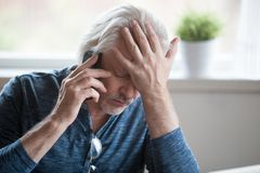 Frustrated mature man feeling upset desperate talking on the pho. Frustrated older mature retired man feeling upset desperate talking on the phone having royalty free stock photos