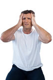 Frustrated mature man with head in hand. Sitting against white background stock photography