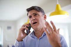 Frustrated Mature Man Receiving Sales Call At Home. Frustrated Mature Man Receives Sales Call At Home stock images