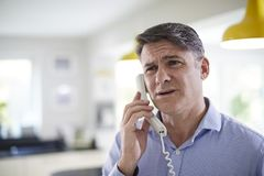 Frustrated Mature Man Receiving Sales Call At Home. Frustrated Mature Man Receives Sales Call At Home royalty free stock photo