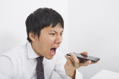 Frustrated mid adult businessman screaming on cell phone in office Stock Images