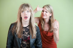 Frustrated Mom. Frustrated mother behind angry daughter in provocative clothing Stock Photography