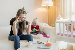 Frustrated mom feeling exhausted. While sitting at home with her child royalty free stock photos