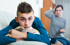 Frustrated mother scolding teenager son. At home. focus on boy Royalty Free Stock Photography