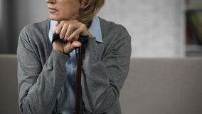 Frustrated old female sitting alone on couch, holding hands on walking stick. Stock photo royalty free stock photos
