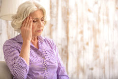 Frustrated old lady has pain in head Royalty Free Stock Image