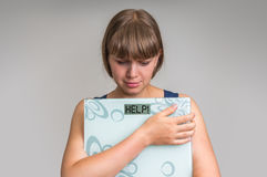 Frustrated overweight woman holding digital scales with HELP! Stock Images